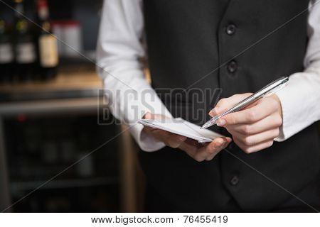Pretty waitress taking an order in a bar