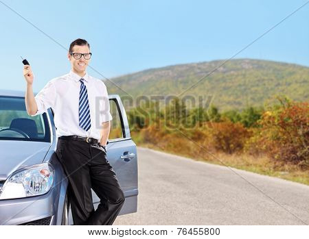 Young man holding key and leaning on a car on an open road
