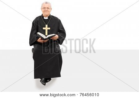 Christian priest reading the bible seated on panel isolated on white background