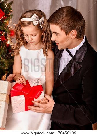 Child with father receiving near Christmas tree.
