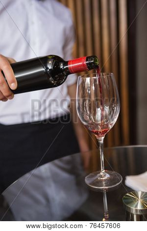 Waiter pouring a bottle of red wine in a bar
