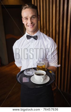 Smiling waiter holding tray with coffee cup and pint of beer in a bar