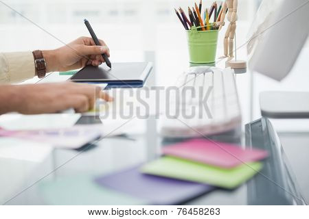 Designer working at desk using digitizer in his office