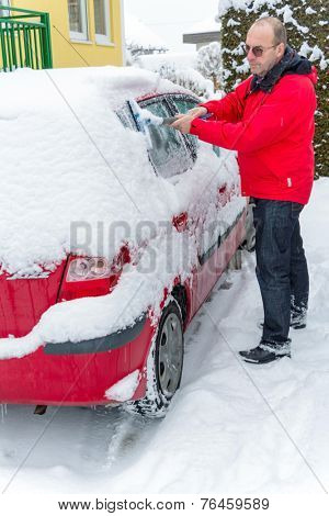 lots of snow on a parked car in the winter.