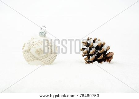 Single White Christmas Bauble With Pine Cone On Snow Isolated
