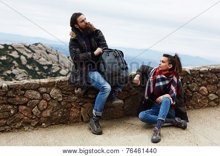 Hikers sitting on mountain hill taking a break after long way
