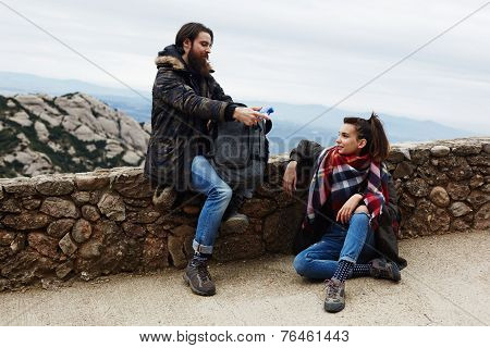 Attractive hiker with beard giving bottle of water to his girl friend