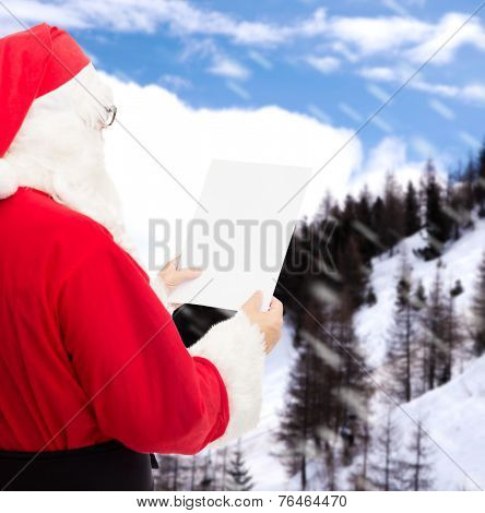 christmas, holidays and people concept - man in costume of santa claus reading letter over snowy mountains background