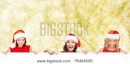 christmas, x-mas, people, advertisement and sale concept - happy women in santa helper hat with blank white board over yellow lights background