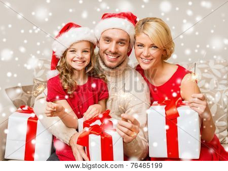 christmas, holidays, family and people concept - happy mother, father and little girl in santa helper hats with gift boxes and sparklers