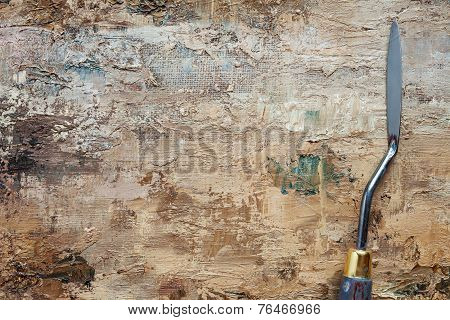 Palette Knife On Artist Canvas With Coating Of Brown Oil Paint