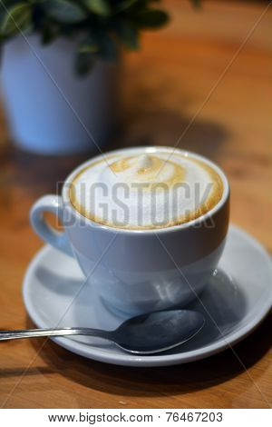 Hot cappuccino on the wooden table