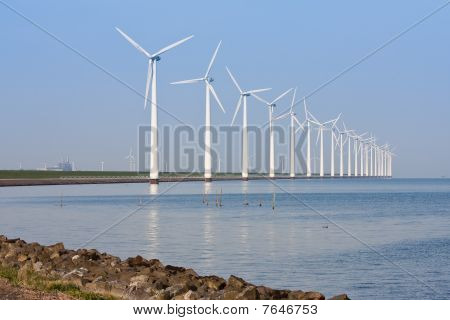 Windmills Along The Coastline, Mirroring In The Calm Sea.