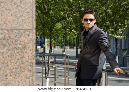 Young Caucasian Man In Jacket And Sunglasses Leans On Metal Handrails