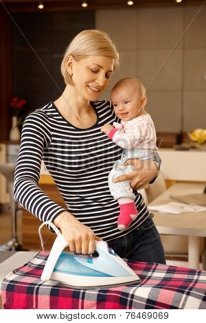 Happy mother ironing at home, holding baby in arm, smiling.