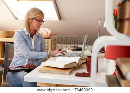 Young woman sitting at desk at home using laptop computer, working, having tablet on lap.