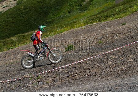 SOCHI, RUSSIA -AUGUST 16, 2014: Off-road motorcycle rider trains in summer mountains