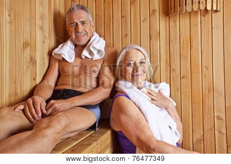 Senior couple sweating and smiling together in a hotel sauna