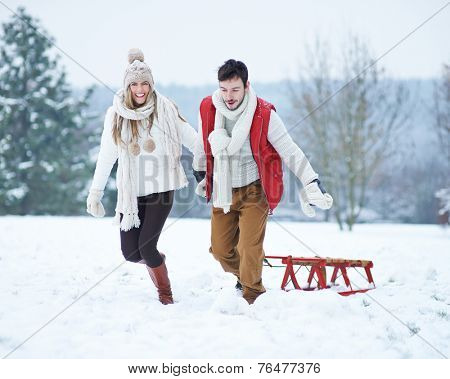 Happy couple pulling sled in winter up a snowy hill