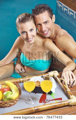Happy couple having breakfast in swimming pool