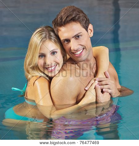 Happy woman embracing smiling man in a hotel swimming pool