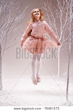 Joyful girl in pink dress jumping in magic forest among bare trees
