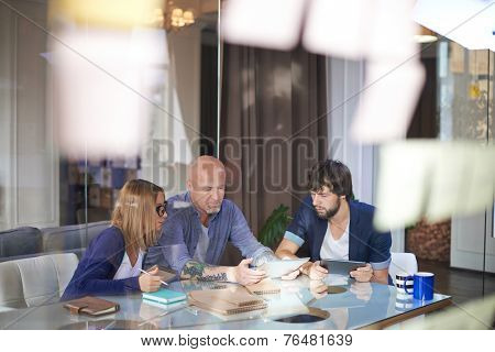 Mature businessman with touchpad presenting his colleagues fresh ideas