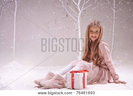 Happy adolescent girl with giftbox looking at camera while sitting in forest of wonders