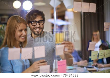 Male and female co-workers reading reminders in office