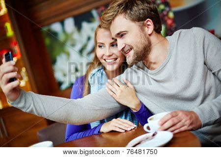 Happy young couple taking their selfie while sitting in cafe