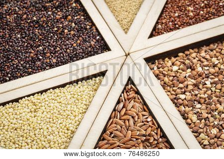 variety of gluten free grains (red and black quinoa, buckwheat, brown rive, amaranth and millet) in a wooden tray, focus on millet and rice