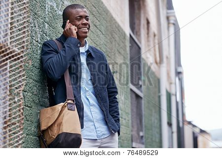 happy young black african man with cell phone having conversation on mobile