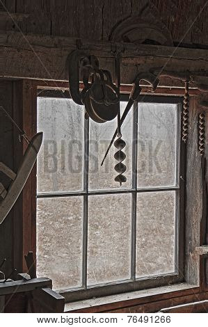 Antique Tools Hanging By The Window Of An Old Blacksmith Shop