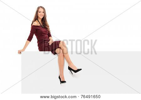 Classy young woman sitting on a blank panel isolated on white background
