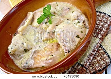 Fish stew in creamy sauce on ceramic pan