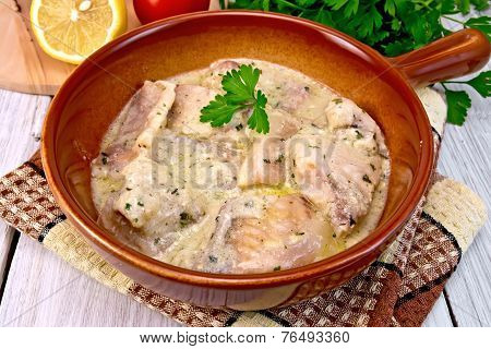 Fish stew in sauce on ceramic pan