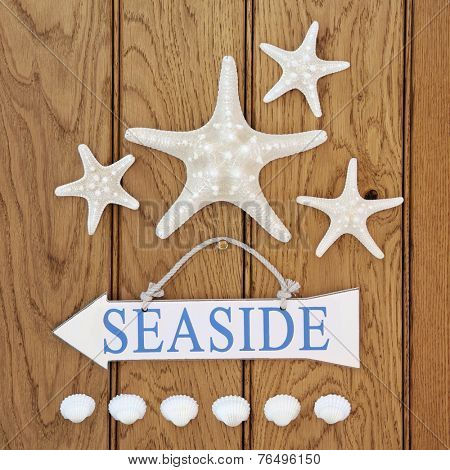 Seaside sign, starfish and cockle shells over old oak background.