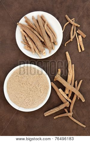 Ginseng ashwagandha herb root and powder over handmade lokta paper background.