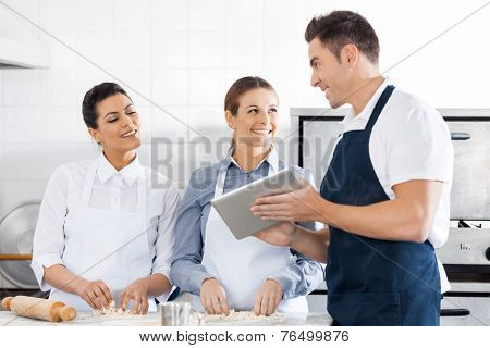 Happy chefs discussing recipe on digital tablet while preparing pasta in commercial kitchen