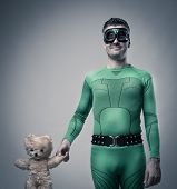 pic of friendship belt  - Green smiling superhero holding a cute soft teddy bear - JPG