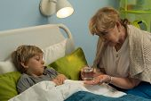 image of grandma  - Grandma caring about his ill grandchild lying in bed - JPG