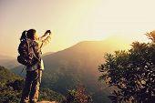 foto of japanese woman  - woman hiker taking photo with smart phone at mountain peak - JPG