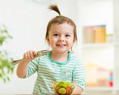 picture of healthy eating girl  - kid girl eating healthy vegetables food at kitchen - JPG