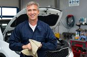 stock photo of auto garage  - Portrait Of A Happy Auto Mechanic Cleaning Hands With Cloth - JPG