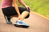 stock photo of twist  - young woman runner hold her twisted ankle - JPG