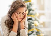 stock photo of sad christmas  - Portrait of stressed young woman near christmas tree - JPG