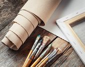 picture of canvas  - Artist canvas in roll canvas stretcher and paintbrushes on old table - JPG