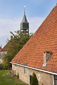 Old Dutch Historic Farmhouse With Churchtower Behind It poster