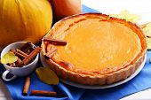stock photo of pumpkin pie  - Composition of homemade pumpkin pie on plate and fresh pumpkins on wooden background - JPG