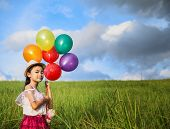 picture of helium  - young asia girl holds tightly to a large bunch of helium filled balloons in nature park - JPG